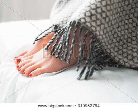 Foot Hygiene. Woman With Red Toenails Sitting On Bed, Hiding Feet Under Blanket.