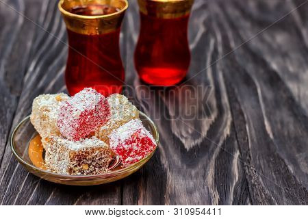 Traditional oriental sweets and traditional Turkish tea on a dark wooden background. Turkish desert-Rahat locum. poster