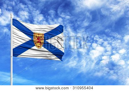 National Flag Of Nova Scotia On A Flagpole In Front Of Blue Sky