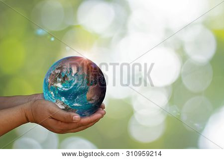 Earth Was Holding In Human Hands On Green Nature Blurred Background. World Environment Day And Green