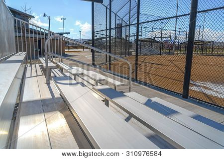 Tiered Bleachers With Metal Handrail At A Sports Field Viewed On A Sunny Day