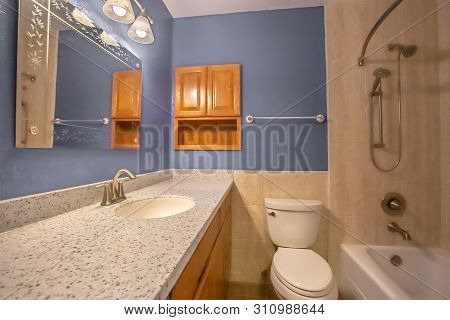 Small Bathroom Interior With Vanity Area Adjacent To The Toilet And Bathtub