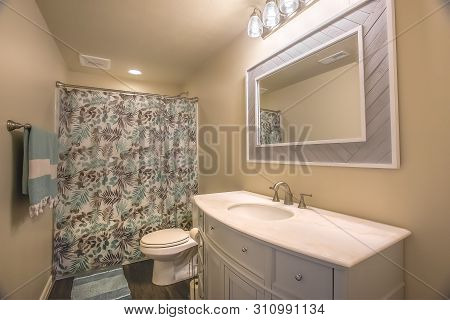 Toilet And Vanity Unit Inside A Bathroom With Wooden Floor And Light Brown Wall