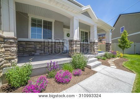 Home Facade With Plants Flowers And Pathway On The Yard In Front Of The Poch