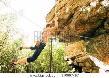 Rock Climber Climbs Bouldering On A Cliff On Forest. Low Angle Of Strong Rock Climbing Man Hanging F