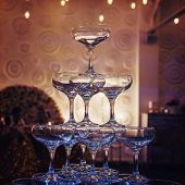 Close up of top tiers of champagne tower at the faint light of a banquet hall. Beautifull built-in set of coupe glasses at a wedding room. Wedding champagne tower is ready for pouring. Luxury wedding poster