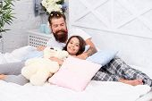 Having fun pajamas party. Slumber party. Happy fatherhood. Close friends. Dad and girl relaxing in bedroom. Pajamas style. Father bearded man with funny hairstyle ponytails and daughter in pajamas. poster
