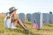 kid in straw hat giving salute while sitting near headstones with american flags poster