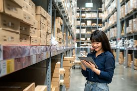 Young Asian Woman Auditor Or Trainee Staff Work Looking Up And Checks The Number Of Items Store By D