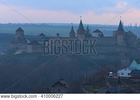 Awesome Landscape View Of Ancient Kamianets-podilskyi Castle During Foggy Evening. Beautuful Meadows