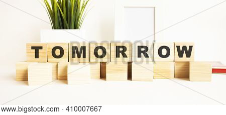 Wooden Cubes With Letters On A White Table. The Word Is Tomorrow. White Background With Photo Frame,