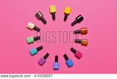 Nail Polish Bottles Laid Out In A Circle Shape Pink Background. Top View With Copy Space