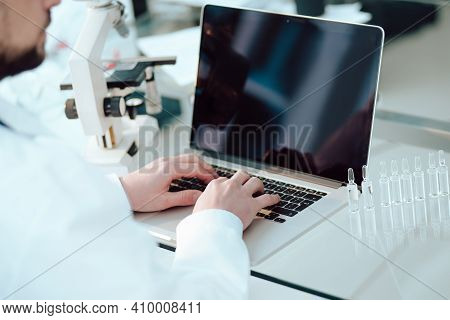 Science Lab Technician Using A Laptop In The Lab.