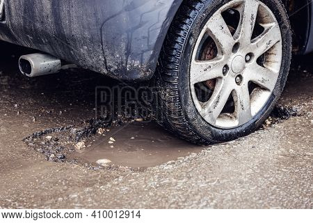 Car Tire In Big Pothole On The Road