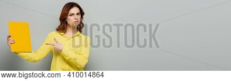Serious Woman In Yellow Blouse Pointing At Notepad On Grey, Banner.