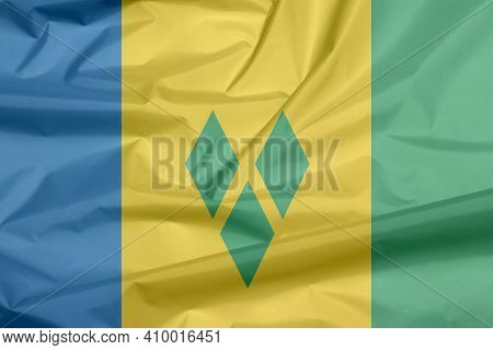 Fabric Flag Of Saint Vincent. Crease Of Saint Vincent Flag Background, Blue Gold And Green With Thre