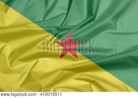 Fabric Flag Of French Guiana. Crease Of French Guiana Flag Background, The Green And Yellow With Red