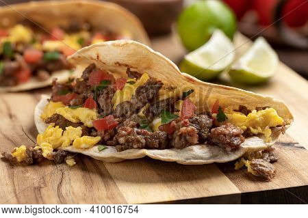 Closeup Of A Breakfast Taco With Scrambled Egg, Sausage And Tomato On A Wooden Cutting Board