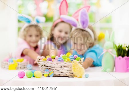 Kids Dyeing Easter Eggs. Children In Bunny Ears Dye Colorful Egg For Easter Hunt. Home Decoration Wi
