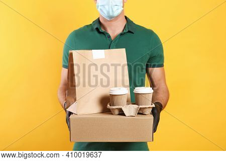 Courier In Medical Mask Holding Packages With Takeaway Food And Drinks On Yellow Background, Closeup