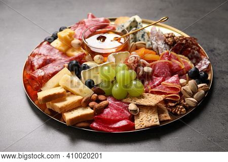 Plate Of Different Appetizers With Honey On Grey Table, Closeup