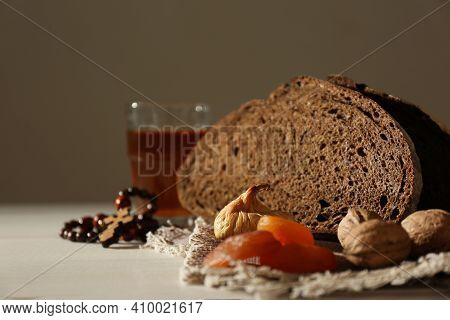 Rosary Beads, Dried Fruits, Walnuts, Bread And Drink On Table. Lent Season