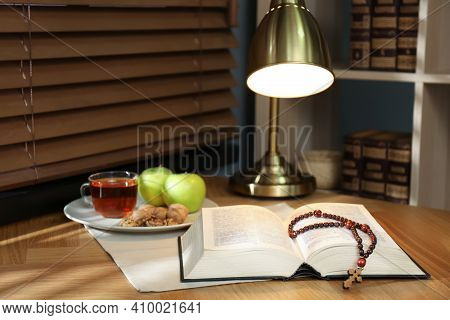 Holy Bible With Prayer Beads And Snacks On Wooden Table Indoors. Great Lent Season