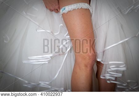 Bride Dresses Garter On The Leg. Picture Of Beautiful Female Legs In Wedding Dress. . High Quality P