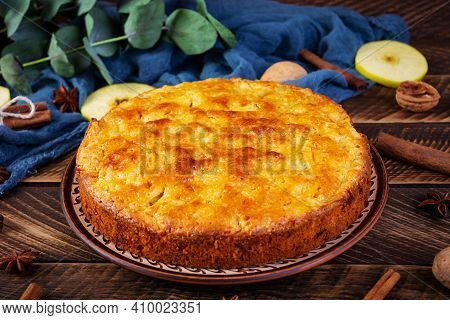 Delicious Homemade Apple Pie On Wooden Background. Apple Pie With Ingredients, Apples And Cinnamon