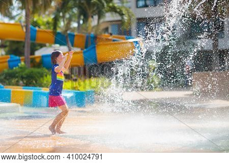 Child Playing Under Tip Bucket In Water Park. Kids Play With Splash Dump Bucket. Family Fun In Amuse