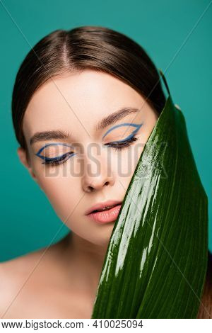 Portrait Of Young Woman With Blue Eyeliner, Near Shiny Leaf Isolated On Green