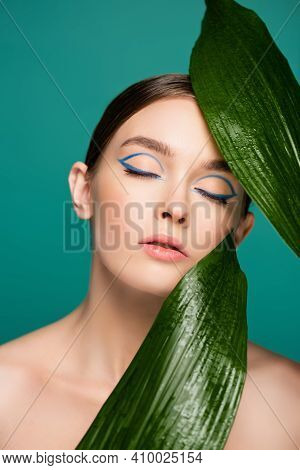 Portrait Of Woman With Blue Eyeliner On Closed Eyes Near Shiny Leaves Isolated On Green