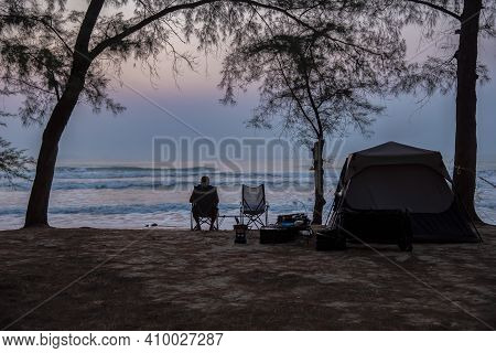 Traveling And Camping Concept - Camp Tent At Night Under A Sky Full Of Stars. Orange Illuminated Ten