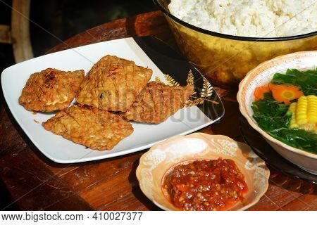 Fried Tempe With Homemade Sambal Terasi, Rice, And Spinach Corn On A Wooden Table