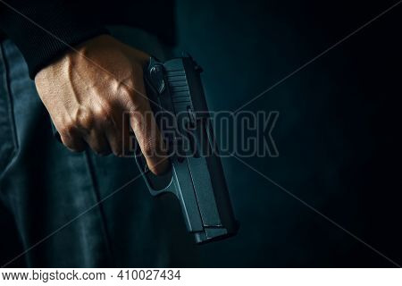 Black Revolver With Drum In Mans Hand. Guy With Gun Down. Firearms For Attack Or Defense. Armed Pers
