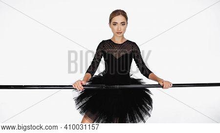 Elegant Ballerina In Tutu Skirt Standing Near Barre On White Background