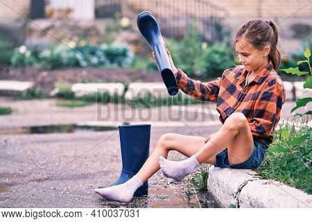 Teenage Girl Sitting On The Curb And Pouring Water From Rubber Boots
