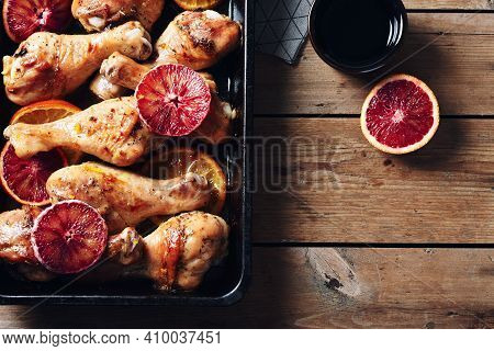 Spice Roasted Chicken Drumstick In Roasting Pan. Baked Chicken Legs With Oranges.