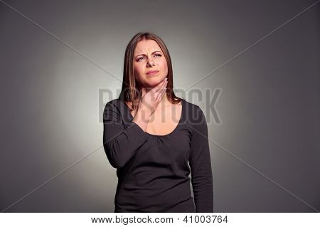 unhappy woman have a throat pain. studio shot over dark background