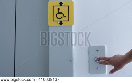 Female Hand Presses The Button To Call The Elevator Inside The Building, Yellow Sign Of The Possibil
