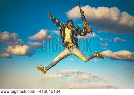 Excited Hunter Man Jumping With Shotgun Gun On Hunt. Crazy Hunter On Sky Background