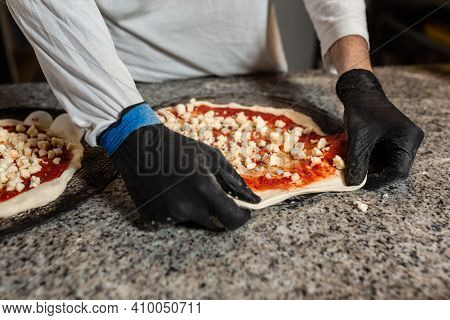 Man Cook Prepares A Pizza In A Italian Restaurant Pizzeria