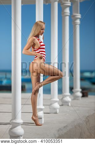 Beautiful Fitness Woman With Perfect Butt And Legs In Red Striped Swimwear Posing On The White-color