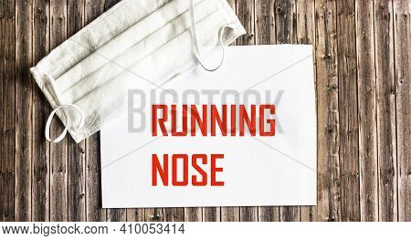 The Word Running Nose Is Written On The Notebook, Next To A Medical Mask