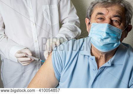 An Elderly Caucasian Man Receives A Dose Of Vaccination In A Nursing Home, Doctor Holding Syringe Su