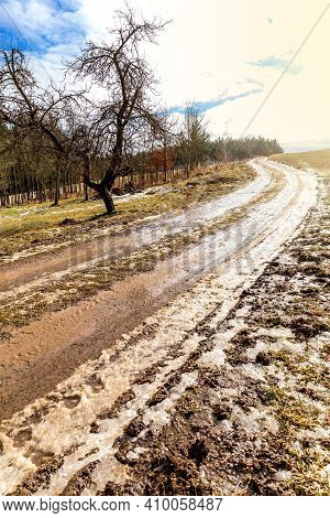 Rural Country Road Covered With Melting Snow And Mud On An Early Spring Day In Czech Republic. Muddy