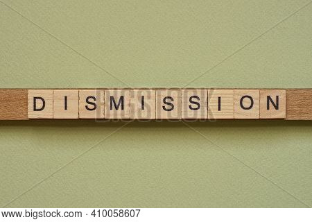 Gray Word Dismission Made Of Wooden Square Letters On Green Background