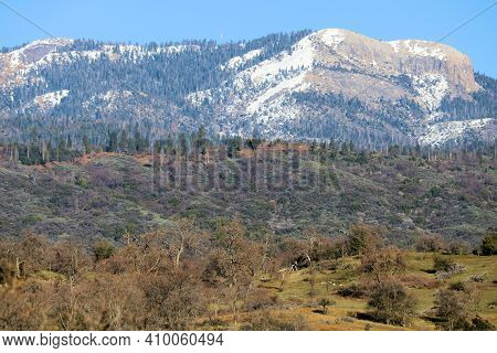 Oak Woodlands And Lush Grasslands On The Foothills With The Rugged Snow Capped Sierra Nevada Mountai