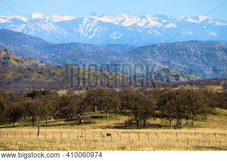 Rustic Wooden Fence Surrounding Grasslands And An Oak Woodland With The Snow Capped Sierra Nevada Mo