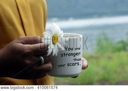 You Are Stronger Than Your Scars. Young Woman Holding A Coffee Cup Or Tea Cup And A Flower In Hands